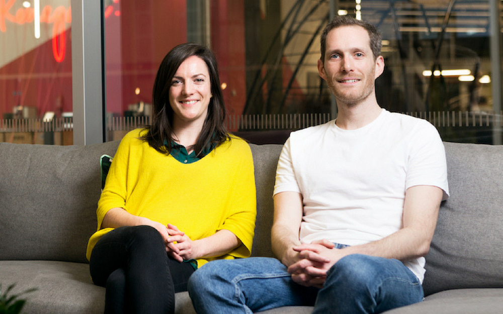 A Woman in a Yellow Jumper and Man in A White T-Shirt On A Sofa