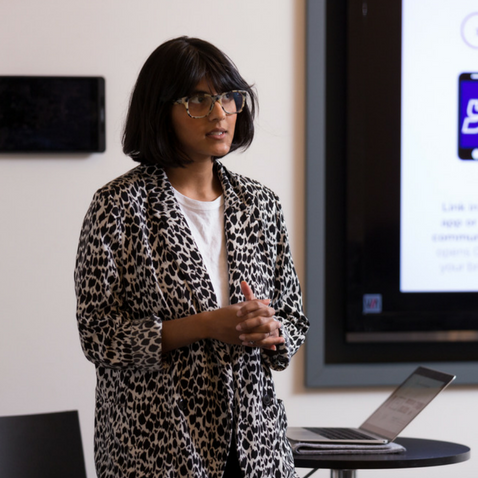 Woman standing infront of a screen doing a presentation for the Alpha Programme