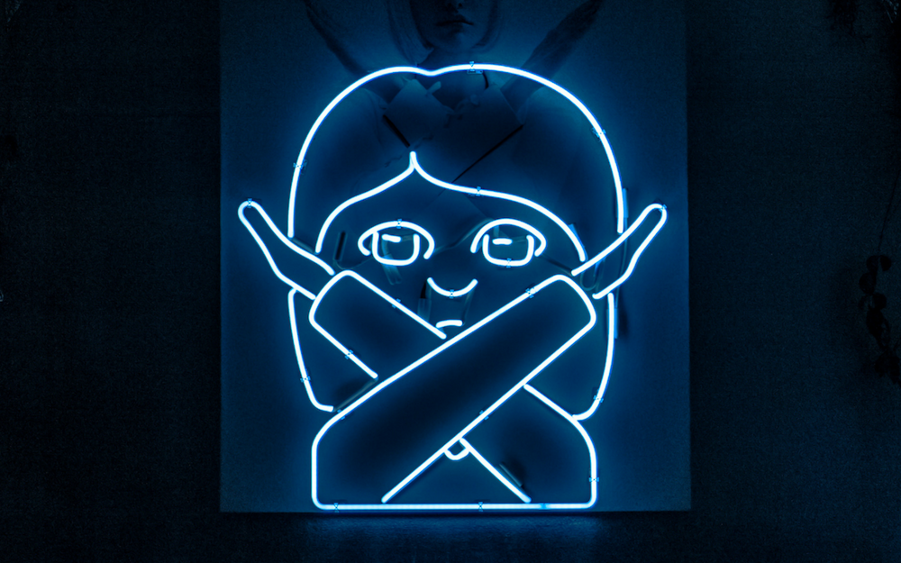 neon emoji of woman with arms crossed