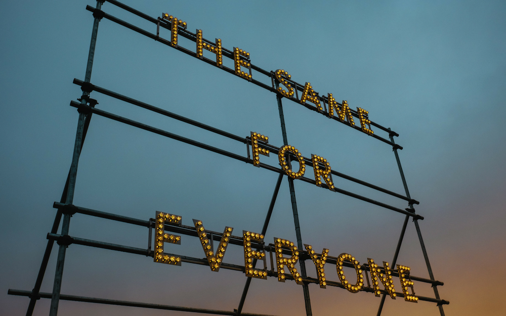 Neon Lightbulb Sign Spelling Out 'The Same for Everyone' At Sunset