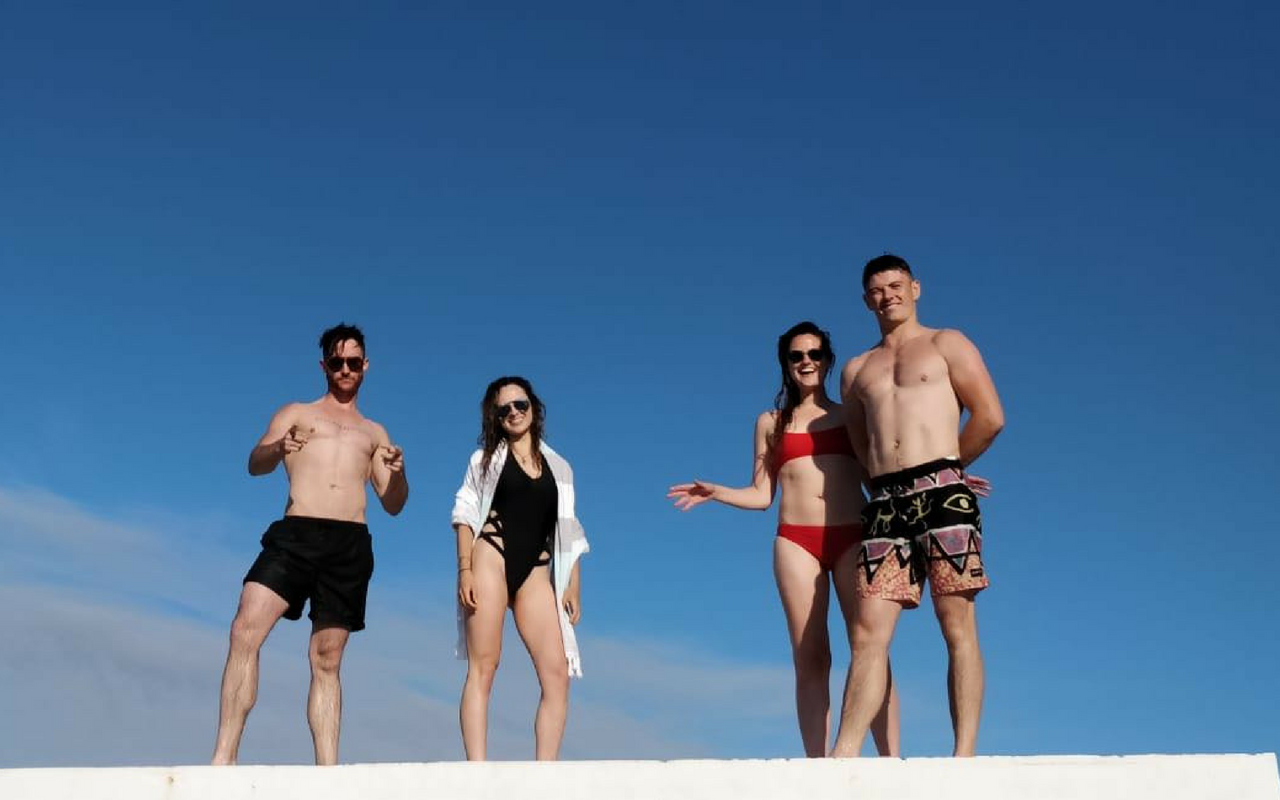 Group of Friends Hanging Out After Swimming Against A Blue Sky