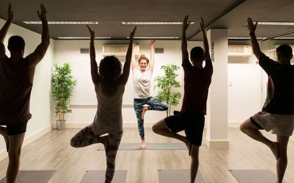 People Doing Yoga In A Darkened Studio