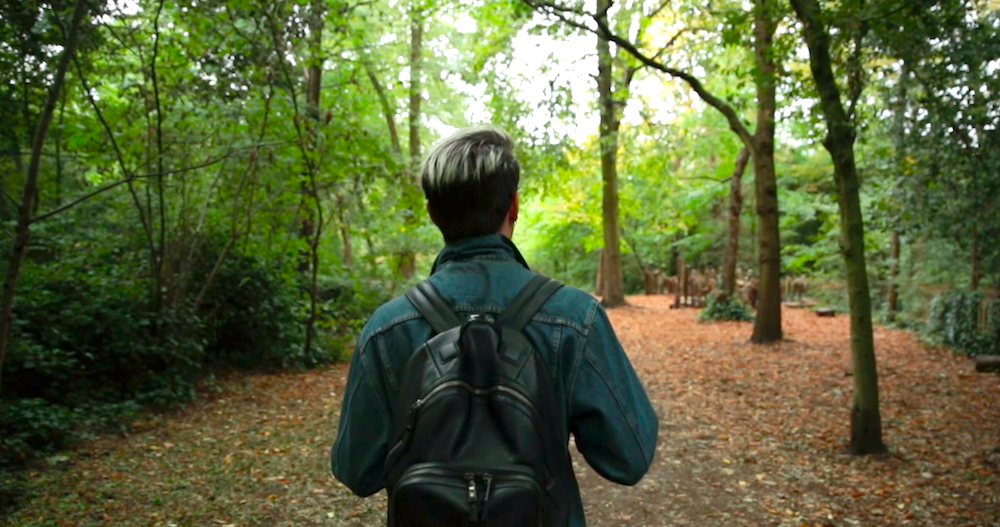 Man Wearing RuckSack Walking Through Woodland
