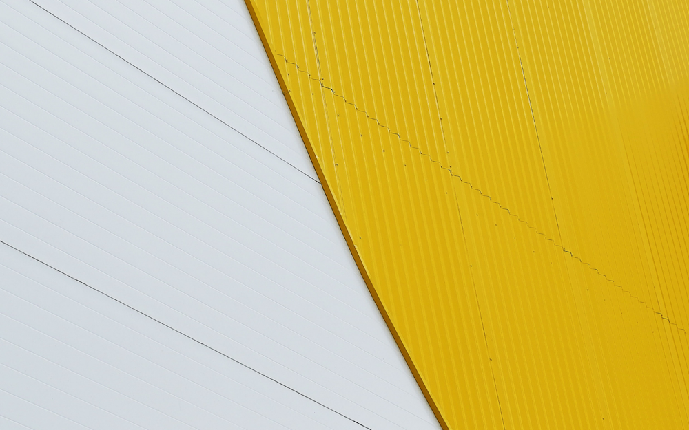 Abstract yellow wall with white striped tiled architecture