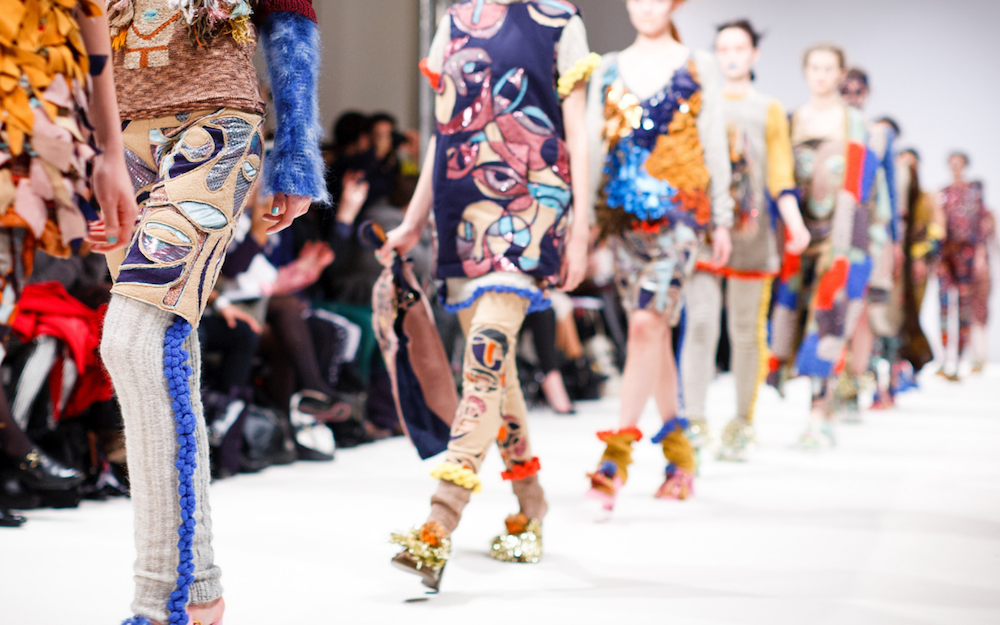 models wearing bright patterned clothes walking on a catwalk