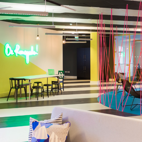 Bright breakout space with neon sign and striped floor at Huckletree D2