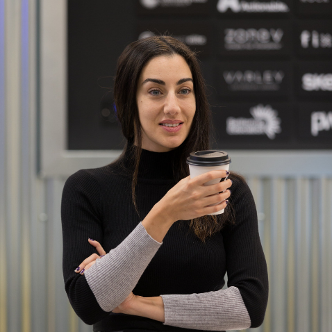 Gabriela Hersham, Huckletree founder, smiling while holding coffee cup