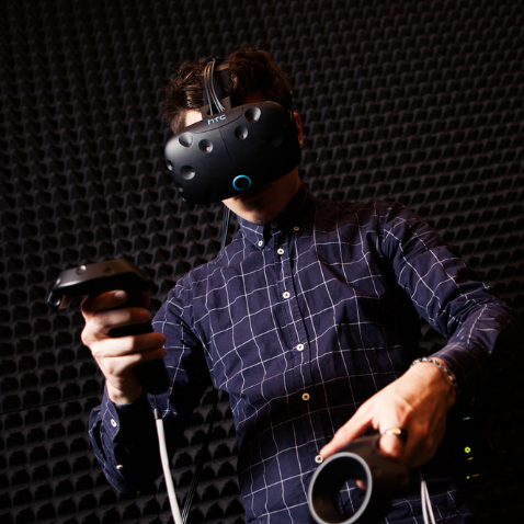 A man playing with VR equipment in a dark room