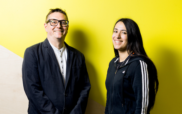 A man and woman leaning against a yellow wall smiling wearing black