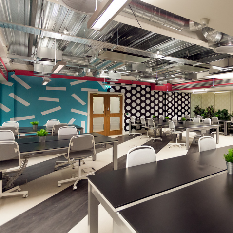 Desks and chairs in patterned room at Huckletree D2