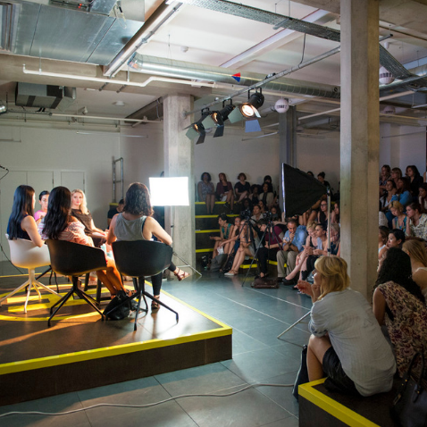 Women speaking to audience on stage