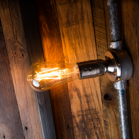 A lightbulb on a wooden wall