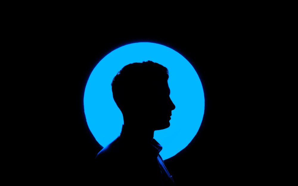 Man standing in silhouette of blue light