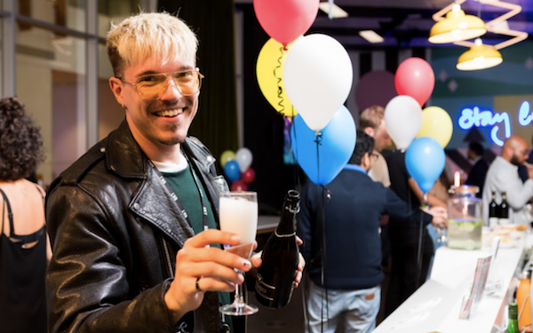 Man smiling at party with glass in hand