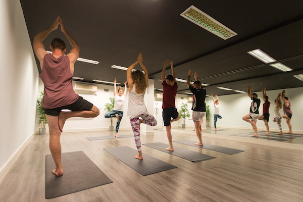 People doing yoga poses in a mirrored studio meets breakout space