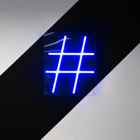 Neon hashtag sign on black and white striped wall