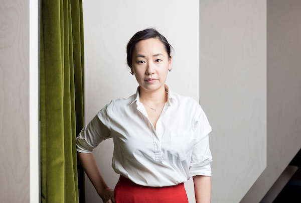 Woman in white shirt stands in front of green curtain