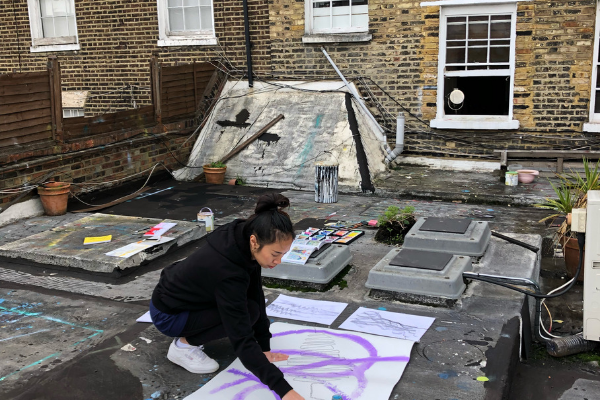 Huckletree Hiring: A woman painting on a canvas on a rooftop