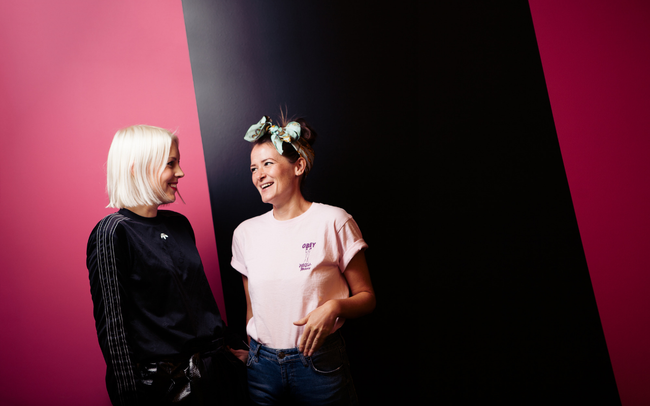 Huckletree Member: Two women smiling at each other with a striped pink and black background