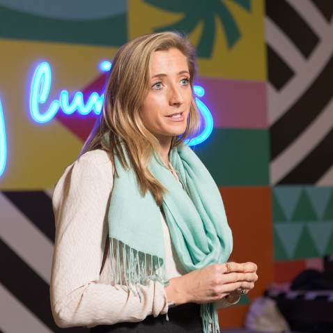 Blonde woman speaking in front of a bright wall