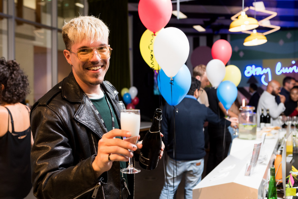 Welcome to May: A man with blonde hair holding a glass of prosecco