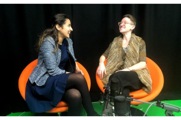 two women laughing sitting on orange chairs