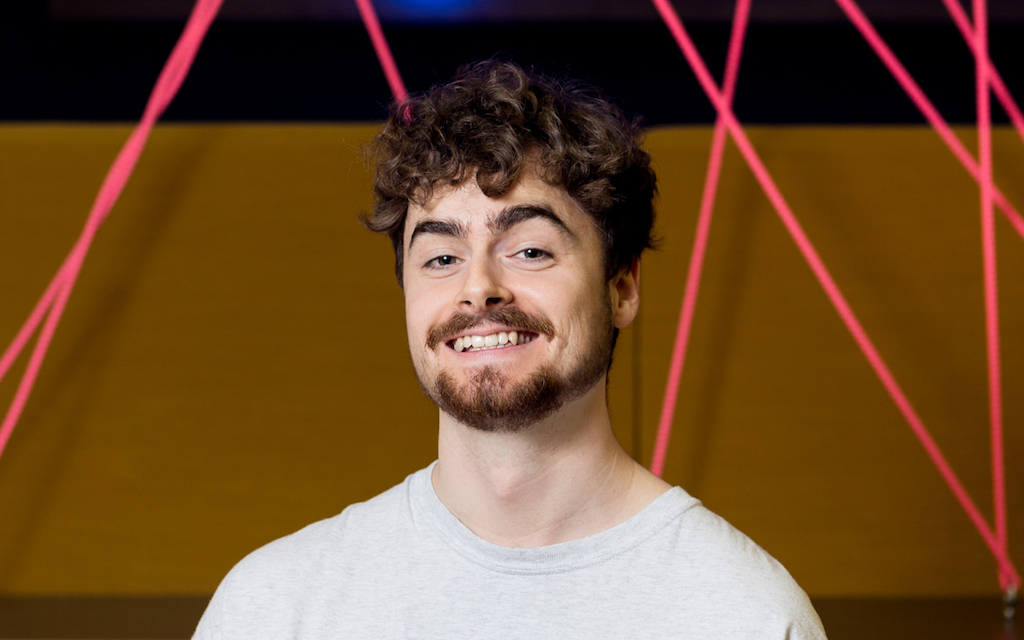Crypto White Man Smiles In Front of Pink Rope Wall